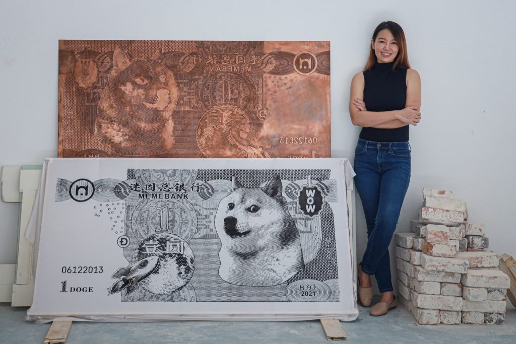woman standing by two giant size art dollar bills