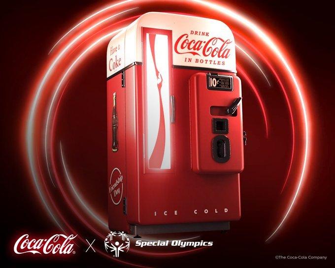 old timey coke machine with colorful circle around whole machine