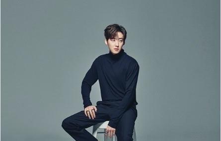 korean man sitting on stool wearing all black